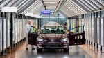 FILE - In this March 5, 2018 file photo, Roland Schulz makes the final check of an e-Golf electric car in the so-called light tunnel in the German car manufacturer Volkswagen's Transparent Factory in Dresden, Germany. (AP Photo/Jens Meyer, File)