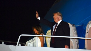U.S. President Donald Trump and first lady Melania Trump walk down the steps of Air Force One at Palm Beach International Airport in West Palm Beach, Fla., Tuesday, Nov. 20, 2018. (AP Photo/Susan Walsh)