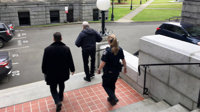 B.C. Legislature Sergeant-at-Arms Gary Lenz, centre, is escorted out of the legislature by security, in Victoria on Tuesday, Nov. 20, 2018. THE CANADIAN PRESS/Dirk Meissner