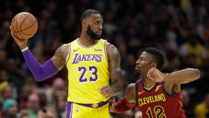 Los Angeles Lakers' LeBron James, left, looks to pass the ball as Cleveland Cavaliers' David Nwaba defends during the first half of an NBA basketball game Wednesday, Nov. 21, 2018, in Cleveland. (AP Photo/Tony Dejak)