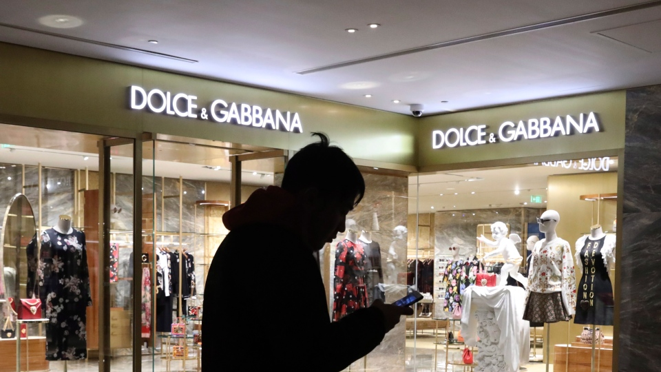 A man walks past a outlet of Dolce & Gabbana in Beijing, China, Wednesday, Nov. 21, 2018. Dolce & Gabbana apologised Wednesday for insulting remarks about China it allegedly made in conversations on Instagram but denied that it was responsible, claiming its accounts had been hacked. (AP Photo/Ng Han Guan)