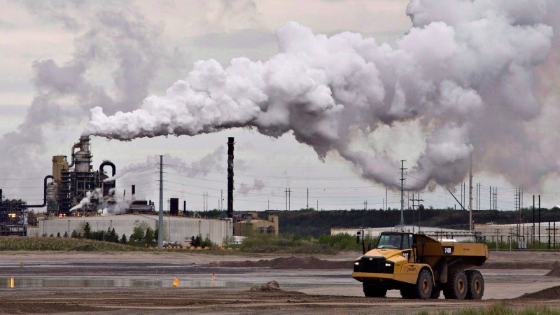 A dump truck works near the Syncrude oil sands extraction facility near the city of Fort McMurray, Alta., on June 1, 2014. THE CANADIAN PRESS/Jason Franson