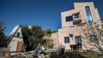 In this Jan. 17, 2016 file photo, Moshe Gordon sits outside his guest house advertised on the Airbnb international home-sharing site, in the Nofei Prat settlement in the West Bank. (AP Photo/Tsafrir Abayov, File)