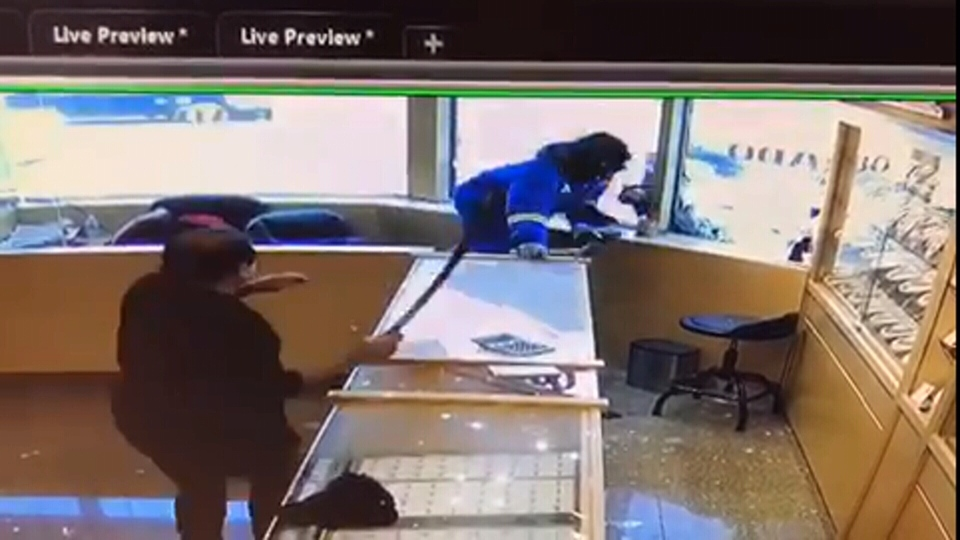 An employee fends off a suspect with a sword during an attempted robbery on Nov. 21, 2018.
