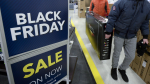 Customers carry a television at Best Buy on Black Friday in Ottawa on November 25, 2016. THE CANADIAN PRESS/Justin Tang