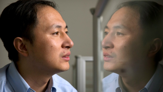 In this Oct. 10, 2018 photo, He Jiankui is reflected in a glass panel as he works at a computer at a laboratory in Shenzhen in southern China's Guangdong province. (AP Photo/Mark Schiefelbein)