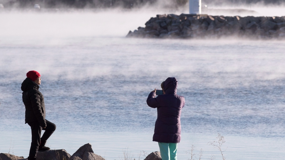 People take picture as mist rises from Lake Ontario during a winter cold snap in the area in Kingston, Ont. on Thursday, Nov. 22, 2018. THE CANADIAN PRESS/Lars Hagberg