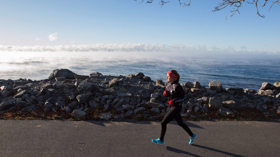 A woman runs beside Lake Ontario as cold mist rises from the lake during a winter cold snap in Kingston, Ont. on Thursday, Nov. 22, 2018. THE CANADIAN PRESS/Lars Hagberg