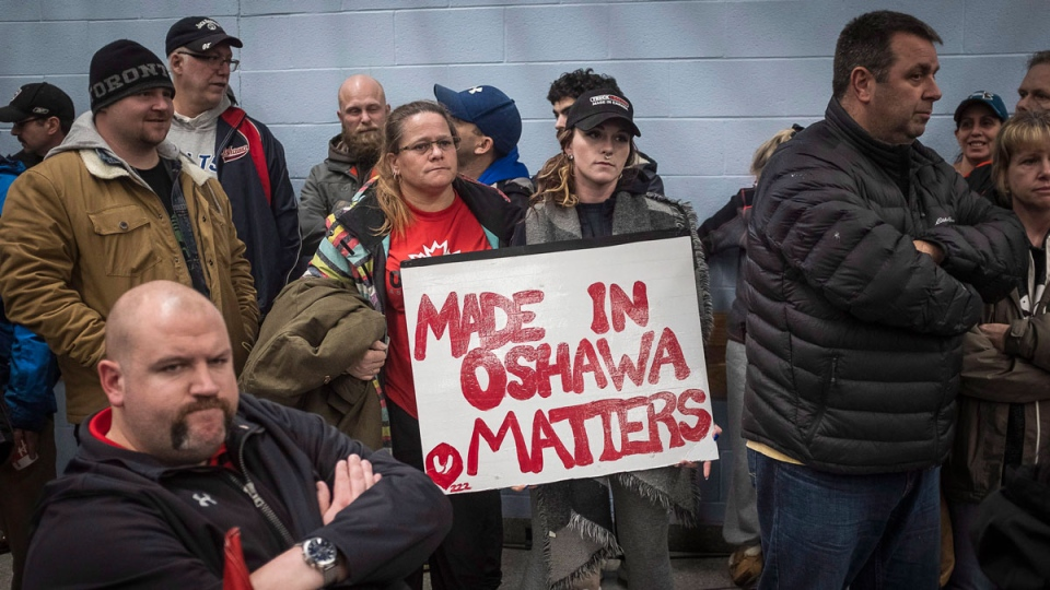 Laurie Nickel, centre left, and her daughter Stephanie hold a protest sign during the UNIFOR union meeting between the workers of Oshawa's General Motors plant with Jerry Dias, president of UNIFOR, Monday, Nov. 26, 2018. The plant, which employs more than 2,500 people, is set to close. THE CANADIAN PRESS/Eduardo Lima