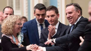 Quebec Premier Francois Legault, right, is congratulated by Quebec Seniors Minister Marguerite Blais, left, while Quebec government House Leader Simon Jolie-Barrette, centre looks on, at the end of the inaugural speech, Wednesday, November 28, 2018 at the legislature in Quebec City. THE CANADIAN PRESS/Jacques Boissinot