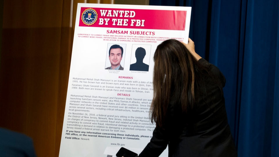 An FBI wanted poster is placed before a news conference held at the Justice Department, Wednesday, Nov. 28, 2018, announcing the indictment against international computer hackers. Two Iranian computer hackers were charged Wednesday in connection with a multimillion-dollar cybercrime and extortion scheme that targeted government agencies, cities and businesses, the Justice Department said. (AP Photo/Jose Luis Magana)