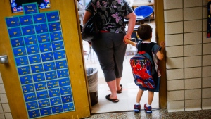 In this Sept. 8, 2015 file photo, a reluctant student is pulled into the first day of kindergarten at an elementary School in Clio, Mich. (Christian Randolph/The Flint Journal via AP, File)