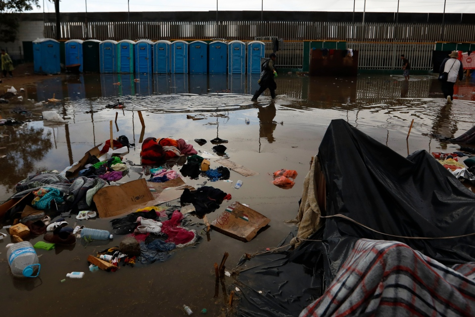 A man walks past flooded belongings, between bouts of heavy rain at a sports complex sheltering thousands of Central Americans in Tijuana, Mexico, Thursday, Nov. 29, 2018. (AP Photo/Rebecca Blackwell)