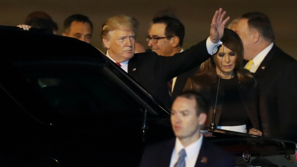 President Donald Trump waves as he and first lady Melania Trump arrive to Ministro Pistarini international airport in Buenos Aires, Argentina, Thursday, Nov. 29, 2018. Trump traveled to Argentina to attend the G20 summit. (AP Photo/Martin Mejia)