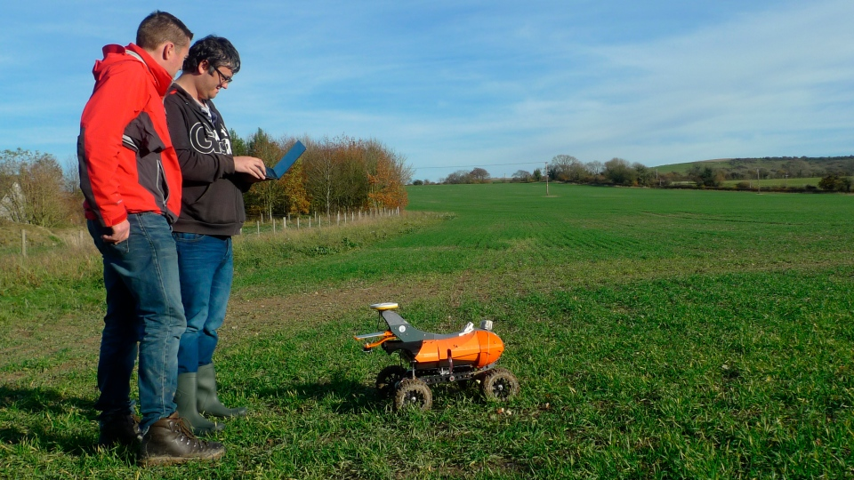 "Joe Allnutt, left, lead roboticist at British startup company the Small Robot Company, with robotics engineer Thomas Burrell operating a farming robot named ""Tom"" as part of a trial in East Meon, southern England, Friday Nov. 30, 2018. (AP Photo / Kelvin Chan)"