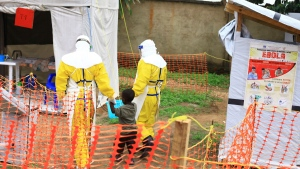 In this file photo dated Sunday, Sept. 9, 2018, health workers walk with a boy suspected as having the Ebola virus at an Ebola treatment centre in Beni, Eastern Congo. (AP Photo/Al-hadji Kudra Maliro, FILE)