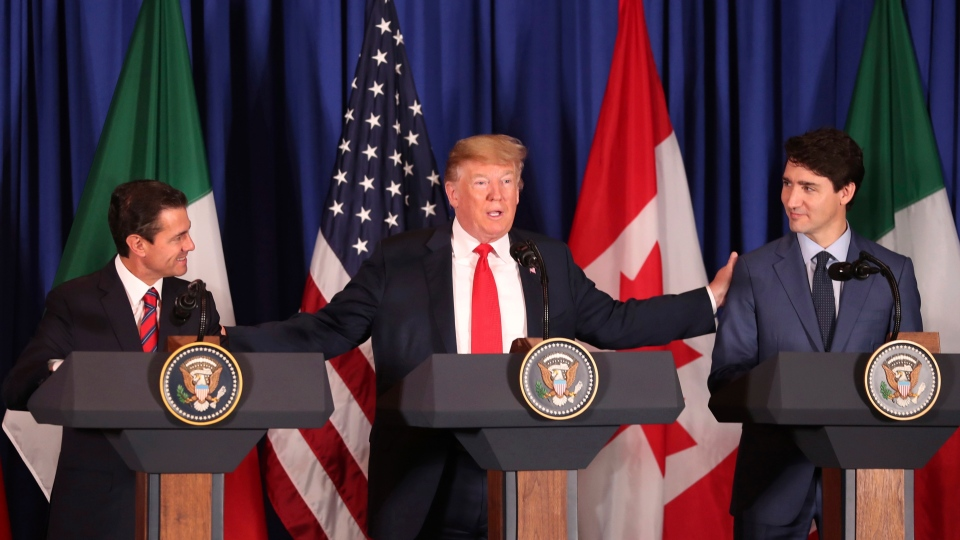 Prime Minister Justin Trudeau, right, stands alongside President Donald Trump, centre, and Mexico's President Enrique Pena Nieto, left, as they prepare to sign a new trade deal to replace NAFTA, during a ceremony at a hotel before the start of the G20 summit in Buenos Aires, Argentina, Friday, Nov. 30, 2018. (AP Photo/Martin Mejia)