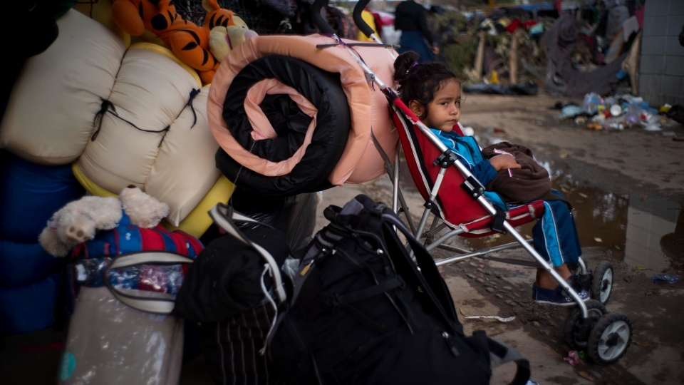 A Honduran migrant girl sits in a stroller as she and her family prepare to leave the shelter where they were staying in Tijuana, Mexico, Friday, Nov. 30, 2018. (AP Photo/Ramon Espinosa)