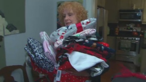 Elizabeth Barry is seen carrying a stack of pyjamas in her home.