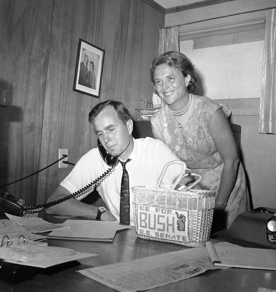 In this June 6, 1964, file photo George H.W. Bush, candidate for the Republican nomination for the U.S. Senate, gets returns by phone at his headquarters in Houston, as his wife Barbara, smiles at the news. (AP Photo/Ed Kolenovsky, File)