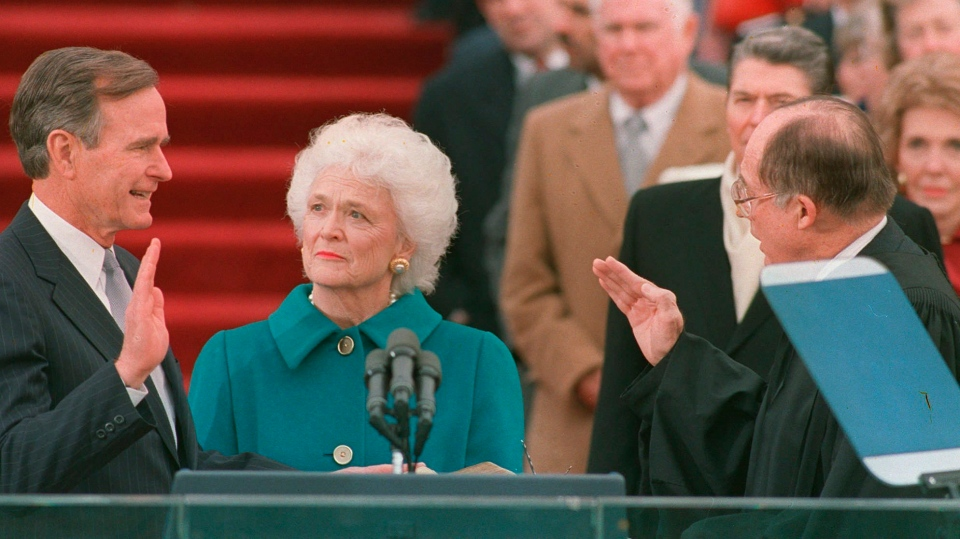 In this Jan. 20, 1989, file photo, President George H.W. Bush raises his right hand as he is sworn into office as the 41st president of the United States by Chief Justice William Rehnquist outside the west front of the Capitol as first lady Barbara Bush holds the bible for her husband. (AP Photo/Bob Daugherty, File)