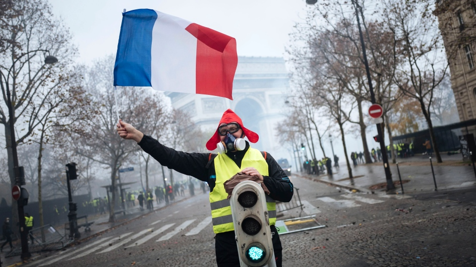 A demonstrator holds a French flag near the Arc de Triomphe during a demonstration Saturday, Dec.1, 2018 in Paris. (AP Photo/Kamil Zihnioglu)