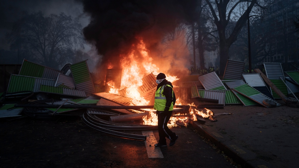 A demonstrator walks past a burning barricade near the Arc de Triomphe on the Champs-Elysees avenue during a demonstration Saturday, Dec.1, 2018 in Paris. (AP Photo/Kamil Zihnioglu)