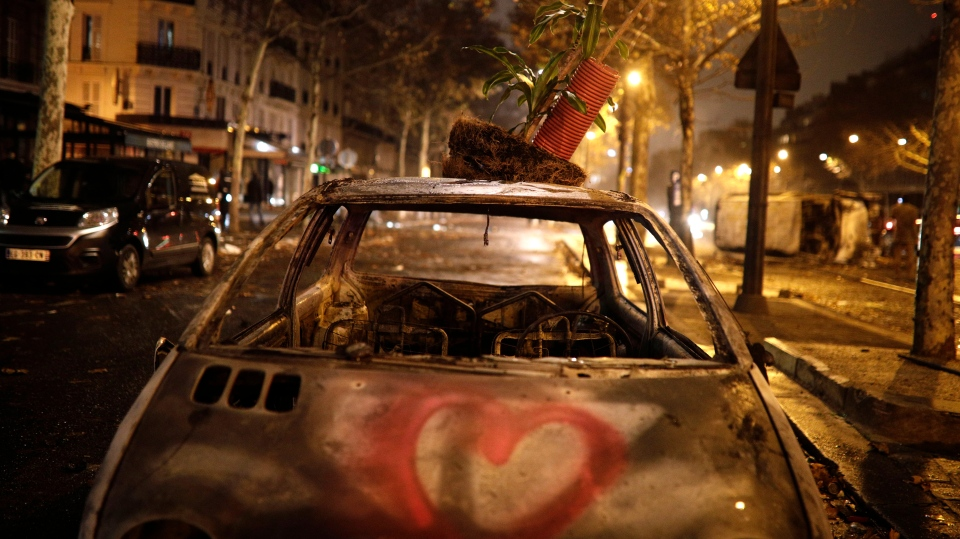 A charred car is pictured near the Arc de Triomphe after the demonstration, Saturday, Dec.1, 2018 in Paris. (AP Photo/Kamil Zihnioglu)