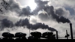 Smoke rising from a factory as a truck loaded with cars crosses a bridge in Paris, France, Friday, Nov. 30, 2018. THE CANADIAN PRESS/AP-Michel Euler
