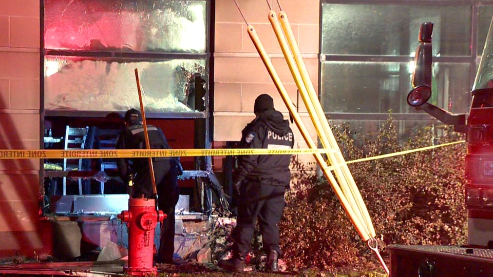 Montreal police examine a broken window at a California Pizza restaurant on Decarie Blvd. on Dec. 3, 2018 (CTV Montreal/Cosmo Santamaria)