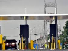 A United States Border Control Agent conducts a routine inspection with a car exiting the Seaway International Bridge traveling from Cornwall Island at the Massena International Plaza near Massena, NY, Friday, June 19, 2009. (AP / Heather Ainsworth)