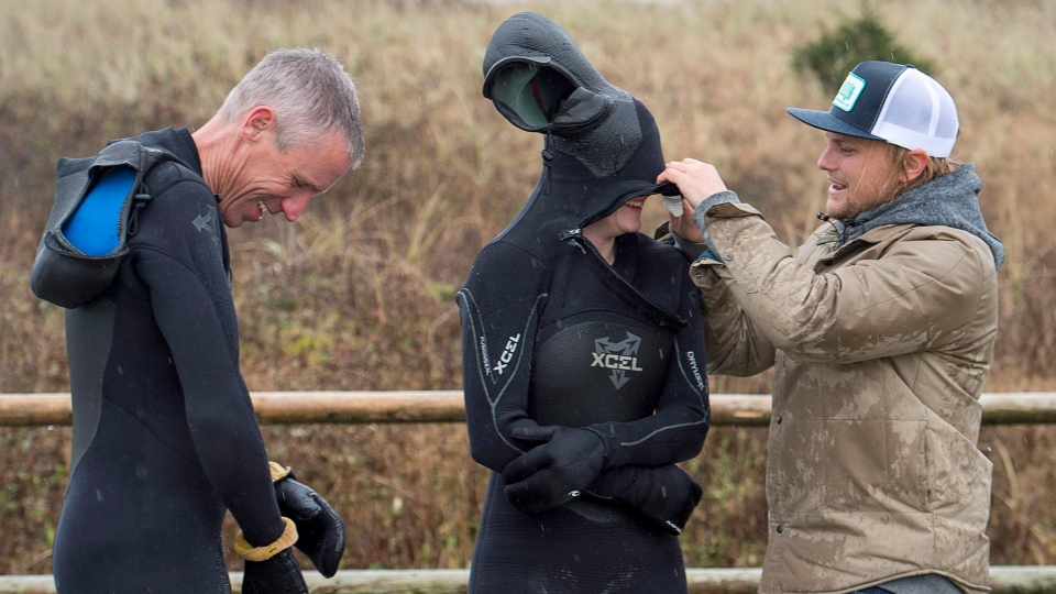 Pete Cove, an instructor at the East Coast Surf School, helps Danile Fahie, left, and his daughter Miranda suit up at Lawrencetown Beach in East Lawrencetown, N.S. on Monday, Nov. 19, 2018.  (THE CANADIAN PRESS/Andrew Vaughan)