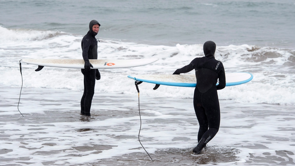 Daniel Fahie and his 15-year-old daughter Miranda brave the water at Lawrencetown Beach in East Lawrencetown, N.S. on Monday, Nov. 19, 2018.  (THE CANADIAN PRESS/Andrew Vaughan)