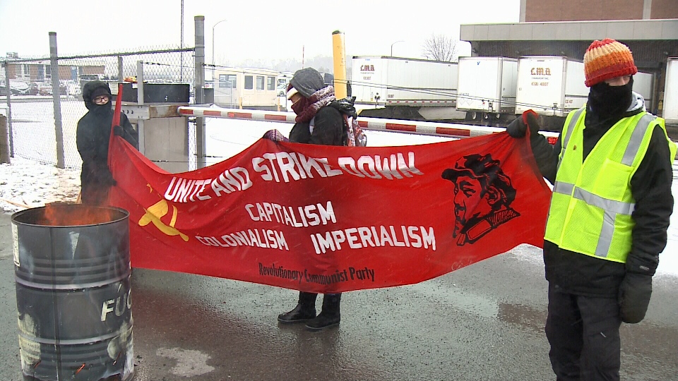 "Protesters holding a banner for the ""Revolutionary Communist Party"" block an entrance to a Canada Post facility in Ottawa, Dec. 3, 2018 (Peter Szperling/CTV Ottawa)"