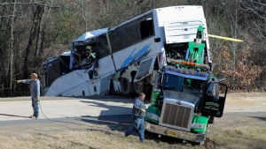 Employees from a wrecker service work to remove a charter bus from a roadside ditch Monday, Dec. 3, 2018, after it crashed alongside Interstate 30 near Benton, Ark. (Josh Briggs/Saline Courier via AP)