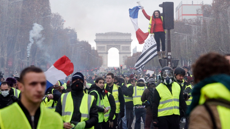 In this Nov 19, 2018 file picture, demonstrators, known as the yellow jackets, invade the famed Champs-Elysees avenue in Paris, France, as they protest against the rise in fuel prices. (AP Photo/Kamil Zihnioglu, File)