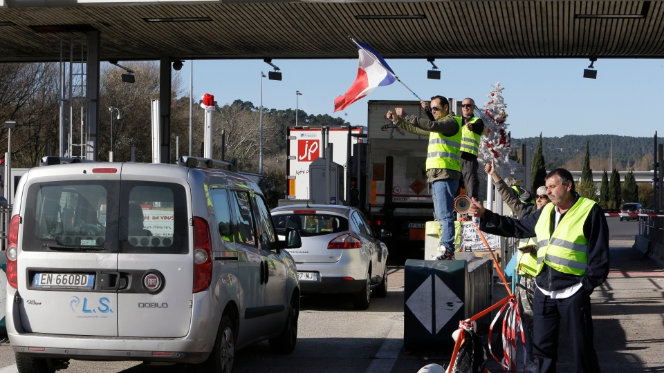 Demonstrators wearing yellow vests open the toll gates on a motorway near Aix-en-Provence, southeastern France, Tuesday, Dec. 4, 2018. (AP Photo/Claude Paris)