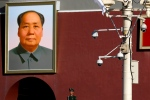 A Chinese paramilitary policeman stands guard near a portrait of the late Chinese leader Mao Zedong and a lamp post mounted with surveillance cameras at the Tiananmen Gate in Beijing, Friday, Oct. 26, 2018. (AP Photo/Andy Wong)