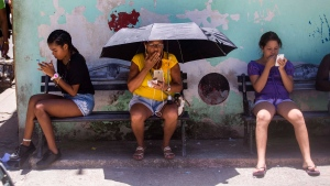 People use their smartphones to surf the internet while sitting outside, in Havana, Cuba, Wednesday, Aug. 22, 2018. (AP Photo/Desmond Boylan)