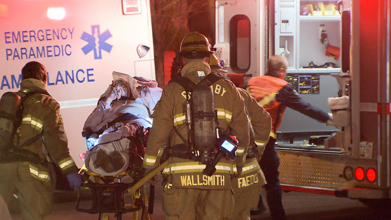 Crews load one injured resident into an ambulance following a house fire in Burnaby, B.C. Dec. 4, 2018.