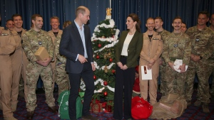 Prince William and Kate Duchess of Cambridge pose with Service Personnel during a Christmas party on RAF Akrotiri in Cyprus, as the Royal couple visit the Sergent's mess to hand out gifts Wednesday Dec. 5, 2018. (Ian Vogler/Pool via AP)