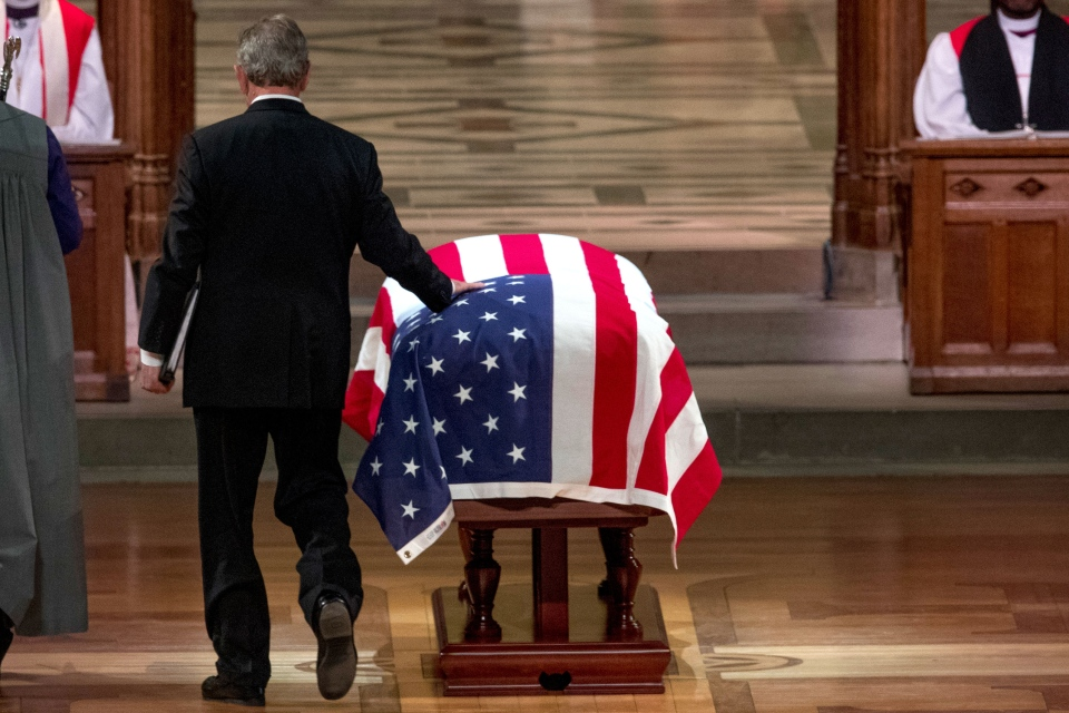 Former U.S. president George Bush touches the flag-draped casket of his father, former president George H.W. Bush, as he prepares to speak during his State Funeral at the National Cathedral, Wednesday, Dec. 5, 2018, in Washington. (AP Photo/Andrew Harnik, Pool)