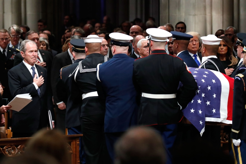 Former U.S. president George W. Bush places his hand over his heart as the flag-draped casket of former president George H.W. Bush is carried by a joint services military honor guard after the State Funeral at the National Cathedral, Wednesday, Dec. 5, 2018, in Washington. (AP Photo/Alex Brandon, Pool)