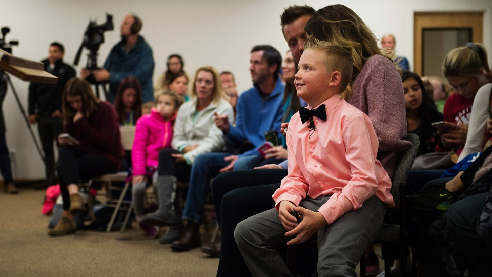 Range View Elementary School third grader Dane Best sits on the lap of his mother, Brooke Best, during a town board meeting where he presented his argument to change a law in Severance that bans snowball fights on Monday, Dec. 3, 2018, at the Town Hall in Severance, Colo. (Timothy Hurst / The Coloradoan via AP)