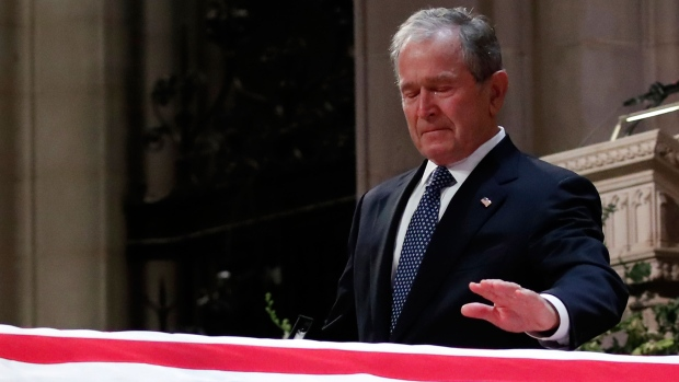 Former U.S. president George W. Bush touches the casket of his father, former president George H.W. Bush, at the State Funeral at the National Cathedral, Wednesday, Dec. 5, 2018, in Washington.(AP Photo/Alex Brandon, Pool)