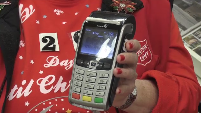 A woman holding a debit machine