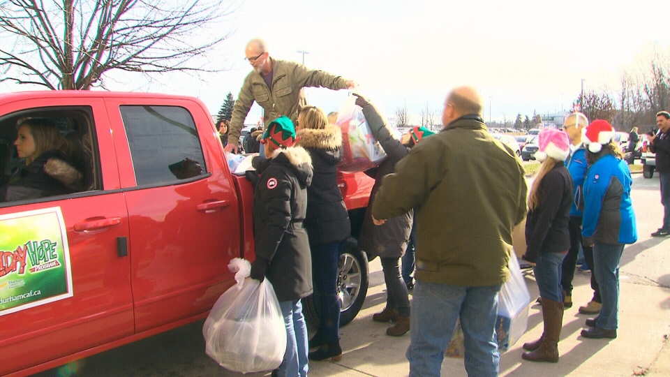 Employees of General Motors unload bags full of gifts for the the Durham Children's Aid Foundation .