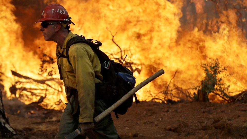FILE -- In this July 28, 2018, file photo, a firefighter walks along a containment line in front of the advancing Carr Fire in Redding, Calif. (AP Photo/Marcio Jose Sanchez, file)