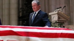 Former President George W. Bush touches the casket of his father, former President George H.W. Bush, at the State Funeral at the National Cathedral, Wednesday, Dec. 5, 2018, in Washington. (AP Photo/Alex Brandon, Pool)