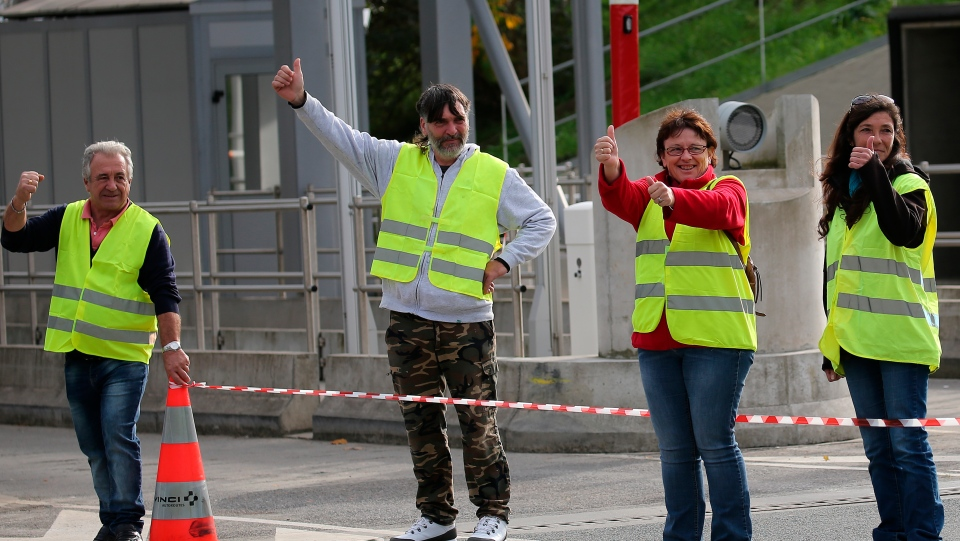 Demonstrators wearing yellow vests protest at the toll gates on a motorway at Biarritz, southwestern France, Thursday, Dec .6, 2018. (AP Photo/Bob Edme)